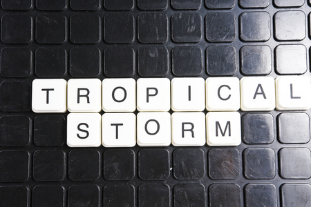 Tropical storm title text word crossword. Alphabet letter blocks game texture background. White alphabetical letters on black background. White educational toy block with words on board table.