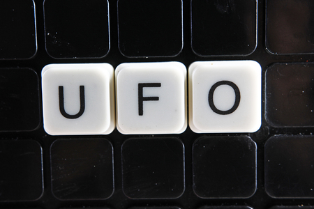ufo,title text word crossword. Alphabet letter blocks game texture background. White alphabetical letters on black background. White educational toy block with words on board table.