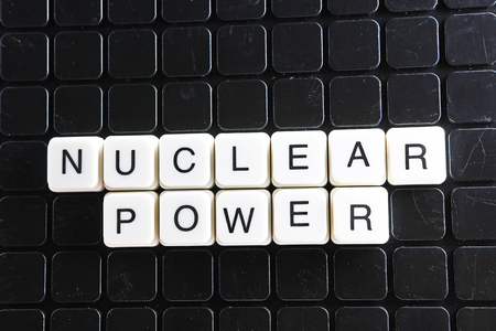 Nuclear power title text word crossword. Alphabet letter blocks game texture background. White alphabetical letters on black background. White educational toy block with words on board table. Stock fotó