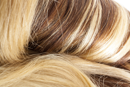 Human hair european hair weft for hair extension. Brown blonde hair texture closeup pattern. Stock Photo