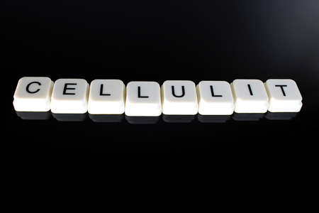 Cellulit text word title caption label cover backdrop background. Alphabet letter toy blocks on black reflective background. White alphabetical letters. White educational toy block with words on mirror board table. Black.