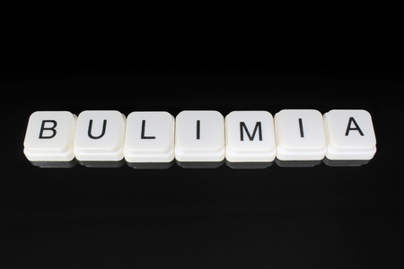 Bulimia, ext word title caption label cover backdrop background. Alphabet letter toy blocks on black reflective background. White alphabetical letters. White educational toy block with words on mirror board table. Black.