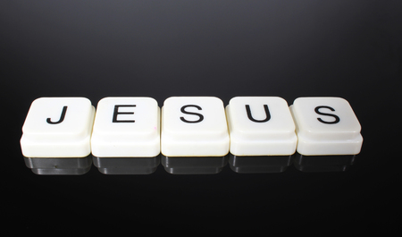 Jesus text word title caption label cover backdrop background. Alphabet letter toy blocks on black reflective background. White alphabetical letters. White educational toy block with words on mirror board table. Stock fotó