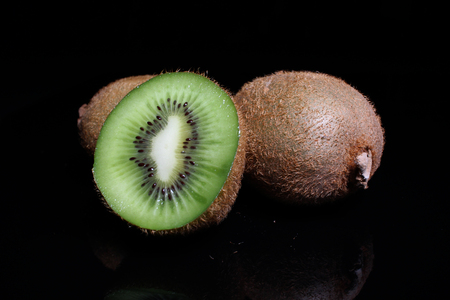 Kiwi kiwis and half kiwi on black background. Studio photo.