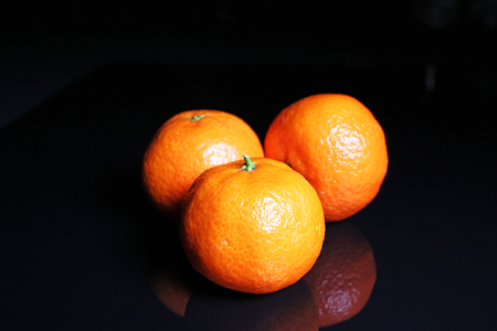 Mandarins. Mandarin citrus orange fruit mandarins on black reflective studio background. Isolated black shiny mirror mirrored background for every concept. Mandarin.