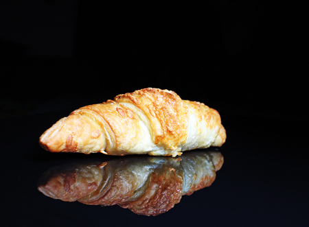 Croissant. Crispy cheesy croissant on black reflective studio background. Isolated black shiny mirror mirrored background for every concept. Croissant.