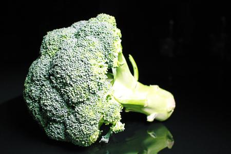 Broccoli. Green whole brokkoli on black reflective studio background. Isolated black shiny mirror mirrored background for every concept. Broccoli.