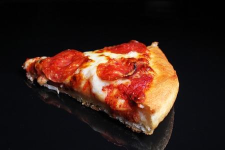 Pizza. Pizza slice on black reflective studio background. Isolated black shiny mirror mirrored background for every concept. Pizza slice. Foto de archivo