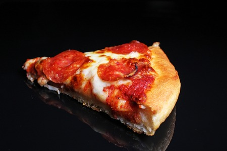 Pizza. Pizza slice on black reflective studio background. Isolated black shiny mirror mirrored background for every concept. Pizza slice. Banque d'images