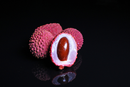 Litchi chinensis. Exotix litchi fruit fruits on black reflective studio background. Isolated black shiny mirror mirrored background for every concept. Litchi.
