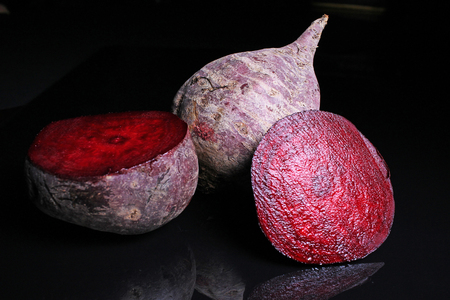 Beet beetroot. Whole and half cutted beet beetroot on black reflective studio background. Isolated black shiny mirror mirrored background for every concept. Beetroot. Stock Photo