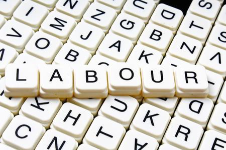 Labour text word crossword title caption label cover background. Alphabet letter toy blocks. White alphabetical letters. Labour.