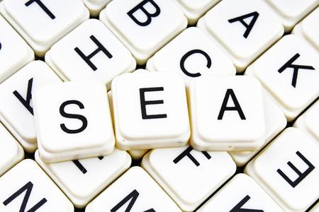 Sea text word crossword title caption label cover background. Alphabet letter toy blocks. White alphabetical letters. Sea.