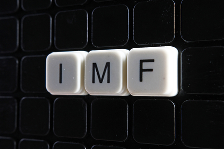 IMF control text word letter toy blocks on black reflective background.