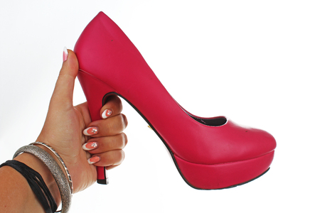 Woman hand holding pink sexy high heels on isolated white cutout background. Studio photo with studio lighting easy to use for every concept. Stock Photo