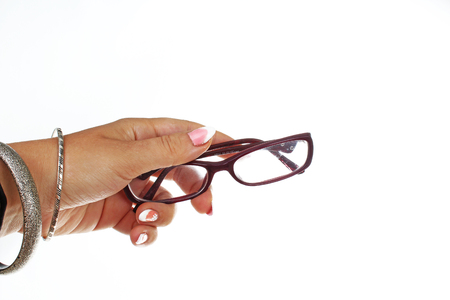 Woman hand holding reading glasses eye wear on isolated white background. Studio photo with studio lighting easy to use for every concept. Stock Photo