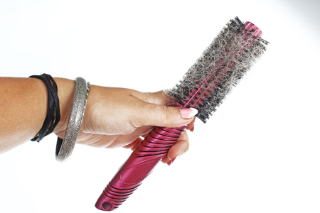 Woman hand holding hairy comb on isolated white background. Studio photo hair loss concept.