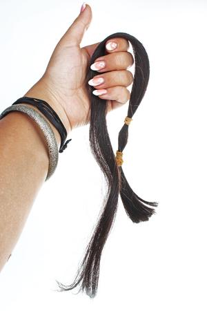 Coda dei capelli umani del blach della tenuta della mano della donna sul fondo bianco isolato del ritaglio. Foto in studio con illuminazione da studio facile da usare per ogni concetto. Archivio Fotografico - 94993920