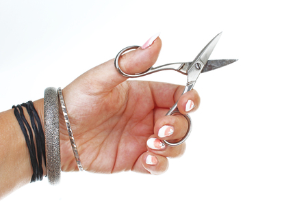 Woman hand holding scissors on isolated white cutout background. Studio photo with studio lighting easy to use for every concept..
