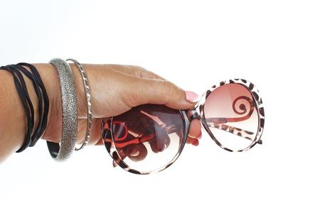 Occhiali da sole della tenuta della mano della donna sul fondo bianco isolato del ritaglio. Foto in studio con illuminazione da studio facile da usare per ogni concetto. Archivio Fotografico - 94993880