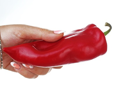 Woman hand holding red pepper paprika on isolated white cutout background. Studio photo with studio lighting easy to use for every concept..