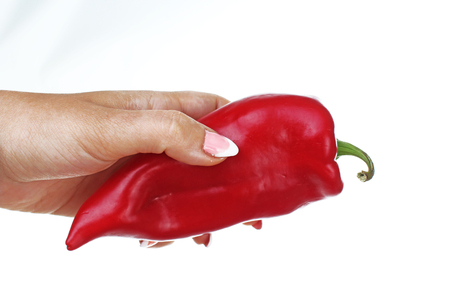 Woman hand holding red pepper paprika on isolated white cutout background. Studio photo with studio lighting easy to use for every concept.. Reklamní fotografie - 94995666