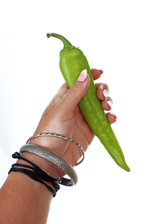 Mano della donna che tiene peperoncino verde su fondo bianco isolato. Foto in studio con illuminazione da studio facile da usare per ogni concetto. Archivio Fotografico - 94995667