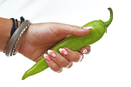 Woman hand holding green hot pepper on isolated white background. Studio photo with studio lighting easy to use for every concept.