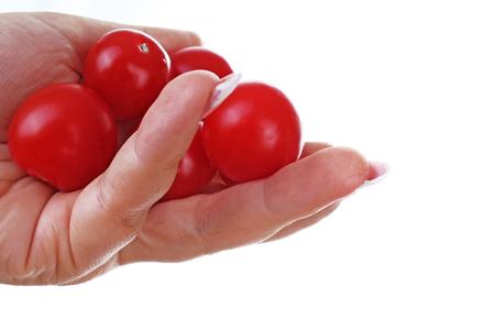Mano della donna che tiene i mini pomodori sul fondo bianco isolato del ritaglio. Foto in studio con illuminazione da studio facile da usare per ogni concetto. Archivio Fotografico - 94995673
