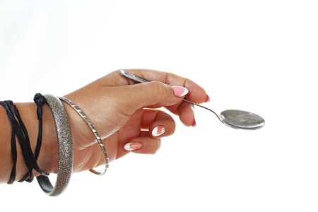 Woman hand holding little spoon on isolated white cutout background. Studio photo with studio lighting easy to use for every concept..