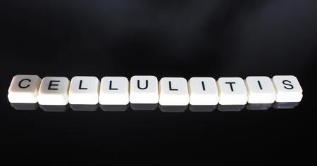 Cellulitis text word title caption label cover backdrop background. Alphabet letter toy blocks on black reflective background. White alphabetical letters..