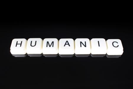 Humanic text word title caption label cover backdrop background. Alphabet letter toy blocks on black reflective background. White alphabetical letters.. Stock fotó