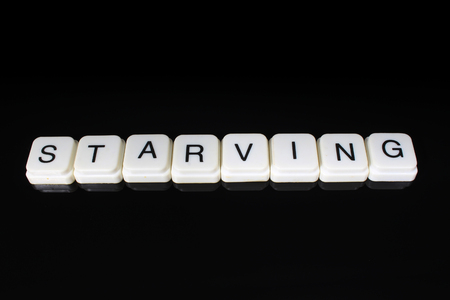 Starving text word title caption label cover backdrop background. Alphabet letter toy blocks on black reflective background. White alphabetical letters..