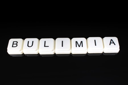Bulimia text word title caption label cover backdrop background. Alphabet letter toy blocks on black reflective background. White alphabetical letters.. Stock Photo