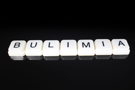 Bulimia text word title caption label cover backdrop background. Alphabet letter toy blocks on black reflective background. White alphabetical letters.. Stock fotó