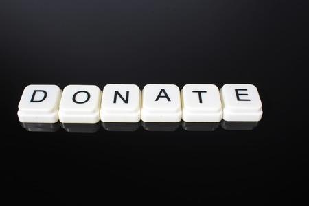 Donate text word title caption label cover backdrop background. Alphabet letter toy blocks on black reflective background. White alphabetical letters.. Stock fotó