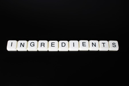 Ingredients text word title caption label cover backdrop background. Alphabet letter toy blocks on black reflective background. White alphabetical letters..