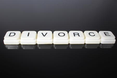Divorce text word title caption label cover backdrop background. Alphabet letter toy blocks on black reflective background. White alphabetical letters. Divorce.