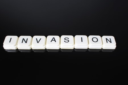 Invasion text word title caption label cover backdrop background. Alphabet letter toy blocks on black reflective background. White alphabetical letters.. Banco de Imagens