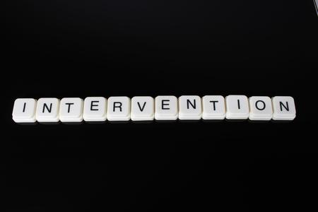 Intervention text word title caption label cover backdrop background. Alphabet letter toy blocks on black reflective background. White alphabetical letters.. Stock fotó