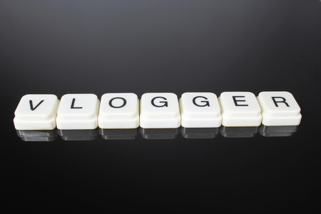 Vlogger text word title caption label cover backdrop background. Alphabet letter toy blocks on black reflective background. White alphabetical letters. vlogger, Stock fotó