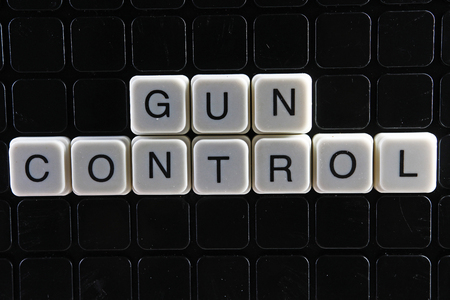 Gun control text word title caption label cover backdrop background. Alphabet letter toy blocks on black reflective background. White alphabetical letters. White educational toy block with words. Banco de Imagens