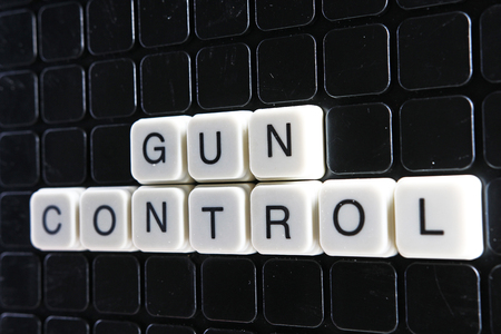 Gun control text word title caption label cover backdrop background. Alphabet letter toy blocks on black reflective background. White alphabetical letters. White educational toy block with words. Stock fotó