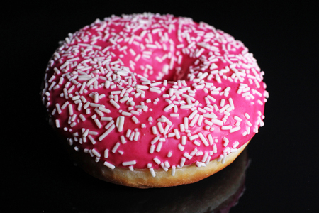 Donut on black reflective studio background. Isolated black shiny mirror mirrored background for every concept. Pink donut..