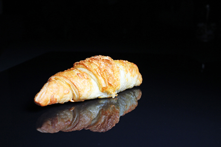 Croissant on black reflective studio background. Isolated black shiny mirror mirrored background for every concept...