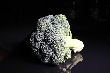 Green whole broccoli on black reflective studio background. Isolated black shiny mirror mirrored background for every concept.