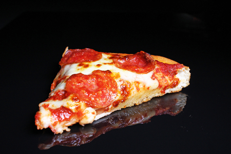 American pizza on black reflective studio background. Isolated black shiny mirror mirrored background for every concept. Stock Photo