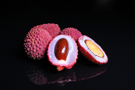 Lychee or litchi litchies or lychees on black reflective studio background. Isolated black shiny mirror mirrored background for every concept.