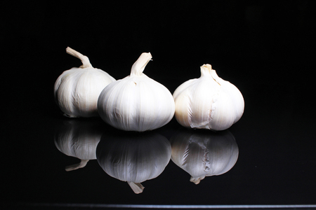 Garlic on black reflective studio background. Isolated black shiny mirror mirrored background for every concept.. Stock Photo