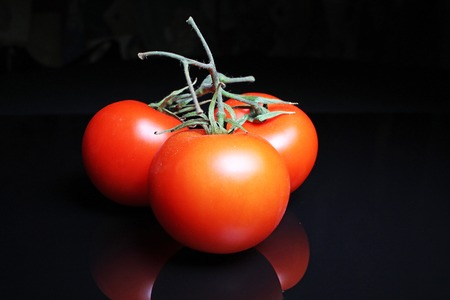 Tomato on black reflective studio background. Isolated black shiny mirror mirrored background for every concept..